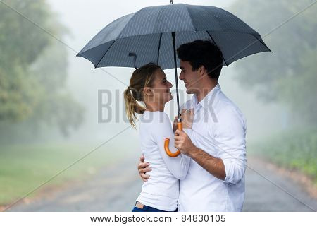 lovely young woman with boyfriend under an umbrella in the rain
