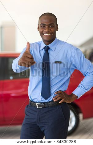 happy young african car salesman thumb up in showroom