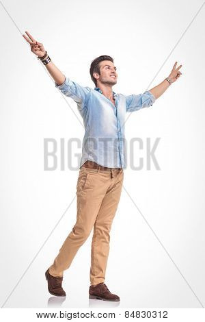 Side view picture of a handsome young fashion man walking with both hands in up, celebrating a victory.