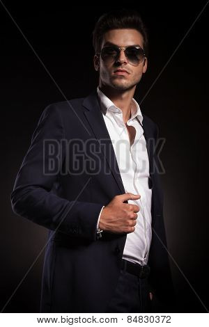 Picture of a young elegant business man looking up while fixing his jacket.