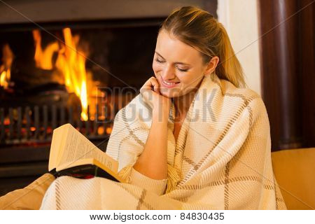beautiful woman reading a book by fireplace