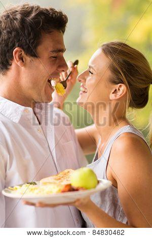 cheerful young woman feeding boyfriend breakfast