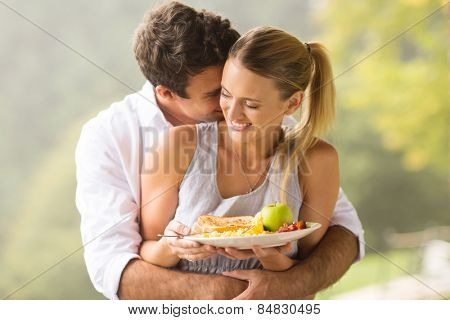 playful young man hugging girlfriend during breakfast time in the morning