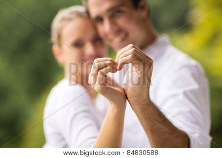 lovely young couple making heart with hands