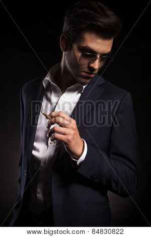 Elegant business man looking down while holding a cigarette in his left hand.