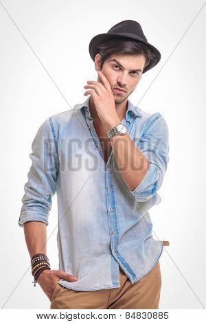 Portrait of a handsome young fashion man holding one hand in his pocket while fixing his beard.