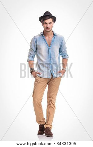 Full boy picture of a young fashion man standing with his hands in pockets on white studio background.