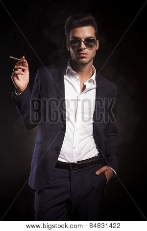 Portrait of a young handsome business man enjoying a cigarette while holding one hand in his pocket.