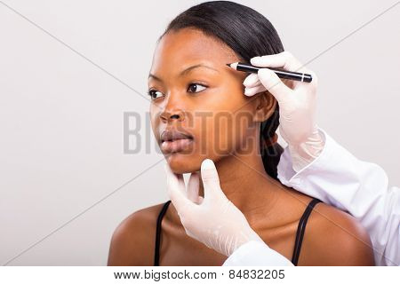 doctor drawing correcting lines african girl face before plastic surgery