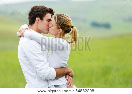 romantic couple kissing outdoors on grassland