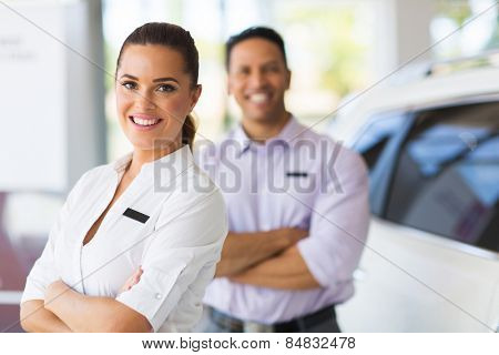 pretty young saleswoman with co-worker on background