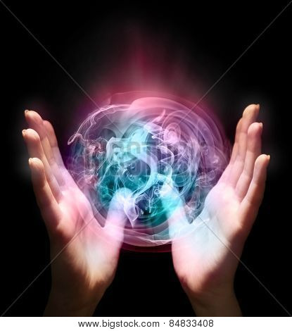 Hands with sphere-shaped color smoke isolated on black