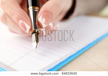 Female hand with pen writing on diary, closeup