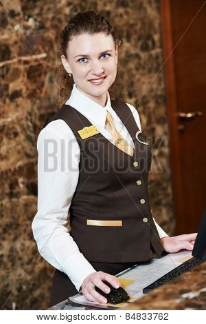 smiling female receptionist passing key card to guest