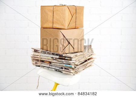Vintage yellow bicycle with newspaper and parcels, on white wall background
