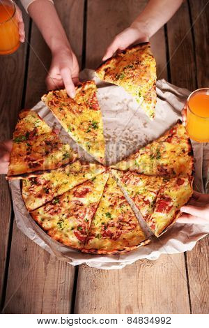Friends hands taking slices of pizza