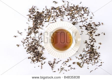 White tea cup with tea and tea leaf