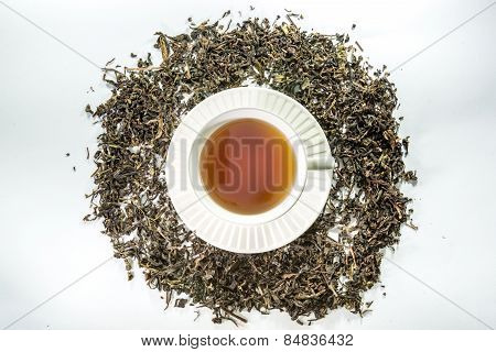 White cup of tea with dried tea leaf