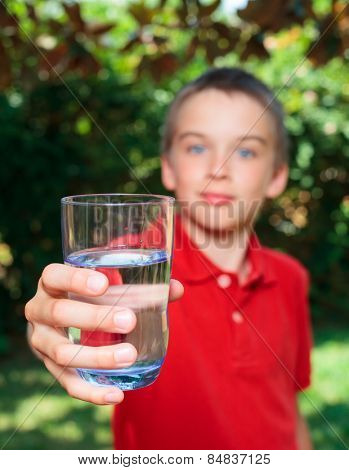 Boy holding glass of water outdoors