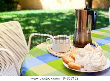 Coffee cup with moka pot and traditional sardinian sweets on a table in a summer garden