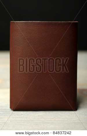 Hand made leather man wallet with money on wooden table
