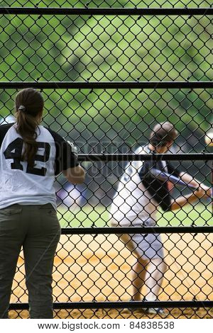 Girl watching and supporting a team mate play baseball