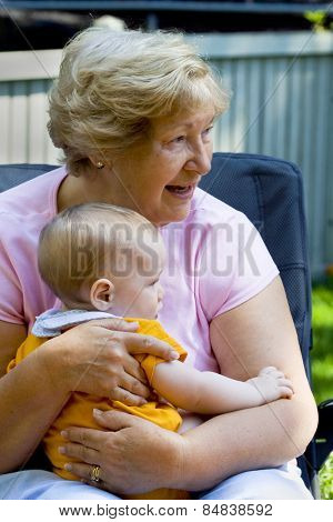 Grandmother holding happy grandson in sunny garden