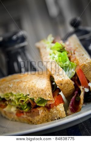Toasted bacon lettuce and tomato sandwich on a white plate