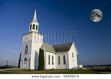 Old white church with full moon rising in background. Moon image used courtesy of NASA (http://earthobservatory.nasa.gov/)