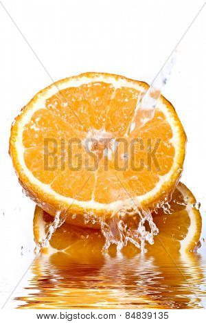 Water splashing down on an orange with reflection