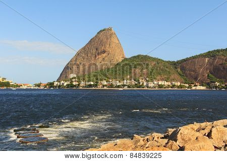 Mountain Sugarloaf From Park Flamengo With Stones And Waves In Guanabara Bay, Rio De Janeiro, Brazil