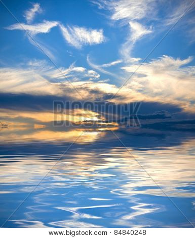 Beautiful sunset with vivid blue sky and light clouds reflected over water