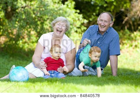 Playing with redheaded twin grandsons with focus on laughing grandparents