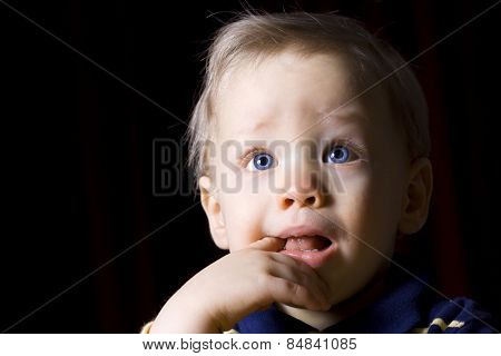 Teething young boy portrait with black background
