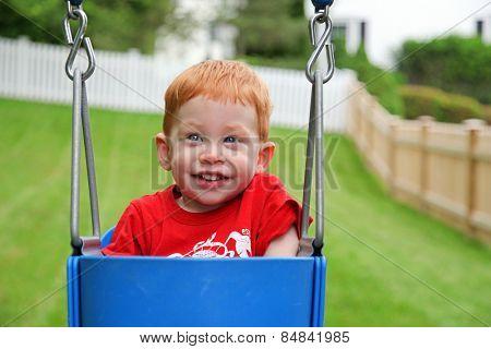 Happy boy sitting in swing outside