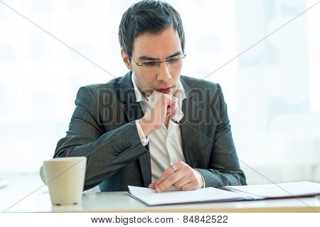Young Executive Thoughtfuly And Attentively Reading A Job Application