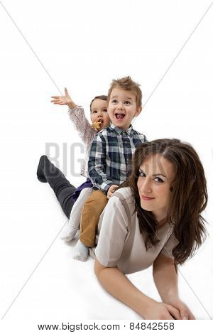 Mother Giving Her Daughter And Son Piggyback Ride Against A White Background