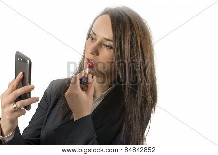 Girl Applies Lipstick Looking At The Phone Like As In A Mirror