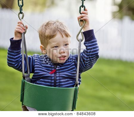 Nervous boy playing on a swing