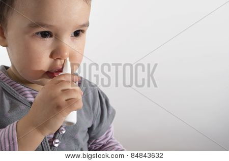 Little Girl Using Nasal Spray - White Background