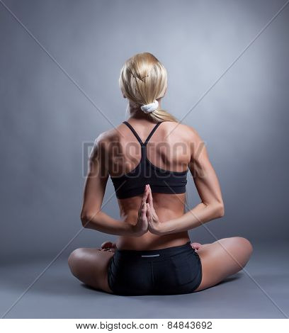 Flexible woman folded hands behind her back