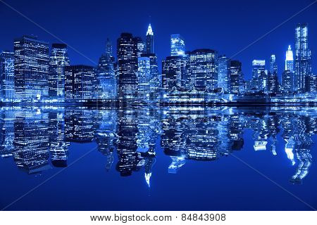 Lower Manhattan in New York City at night with reflection in water with blue hue