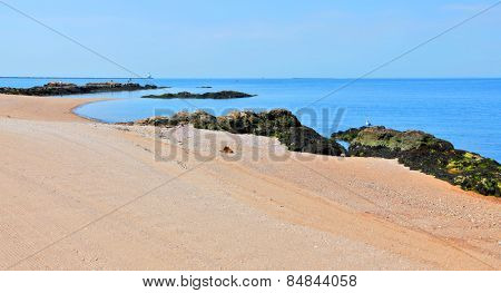 Beautiful empty beach with sand and rocks along shoreline