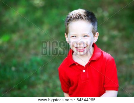 Happy boy outside smiling wearing a red shirt