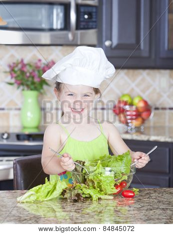 Cute little girl playing with a bowl of salad