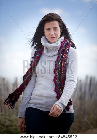 Pretty woman wearing a scarf and sweater walking