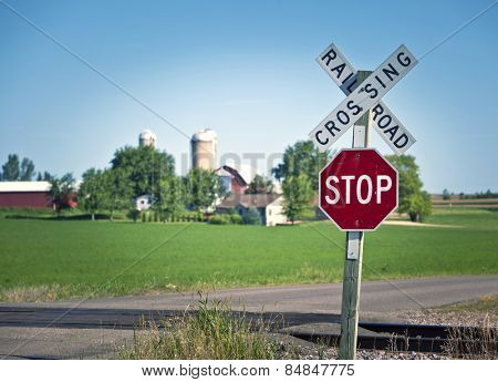 Railroad crossing and stop sign in farmland