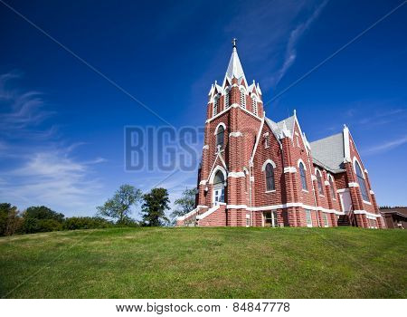 Rural brick christian church set against blue sky