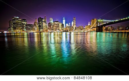 Lower Manhattan and Brooklyn Bridge in New York City at night with reflection in water