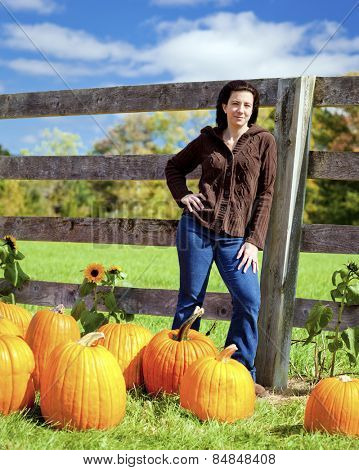Woman at pumpkin patch selecting a pumpkin